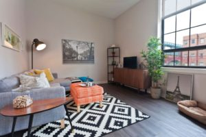 Apartment living room facing large picture windows at Chocolate Works in Philadelphia