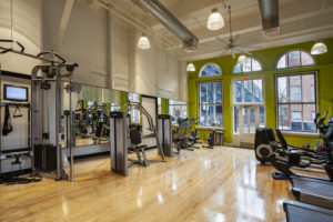 Fitness center with weights and cardio equipment at Chocolate Works Old City apartments