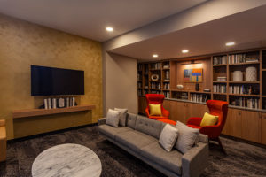 Resident library with couch and tv at Chocolate Works apartments in Old City
