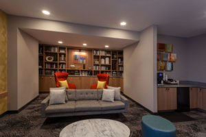 Resident library with TV, kitchen, and workstations at Chocolate Works apartments in Old City